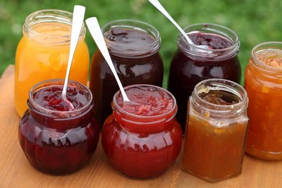 Glass with strawberry, cherry, orange, plum, blackcurrant and peach jam and spoons